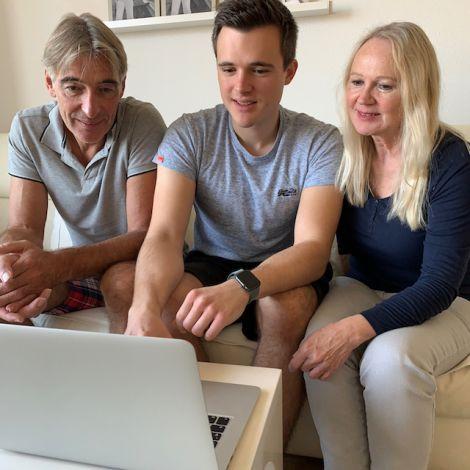 Dominik und seine Eltern sitzen auf dem Sofa und schauen sich auf einem Laptop Bilder von seinem Auslandsaufenthalt an.