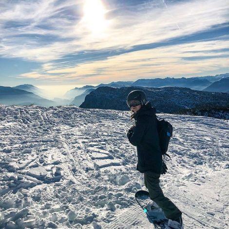 Studentin Carina steht in voller Snowboardmontur auf einem verschneiten Berg. Im Hintergrund ist ein Gebirge zu sehen.