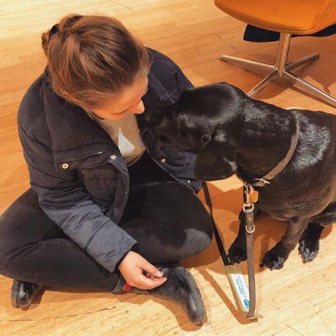 Studentin Sophie sitzt auf dem Boden neben einem schwarzen Labrador.