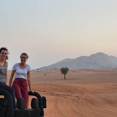 Zwei junge Frauen sitzen oben auf einem Jeep-Cabrio in der Wüste.