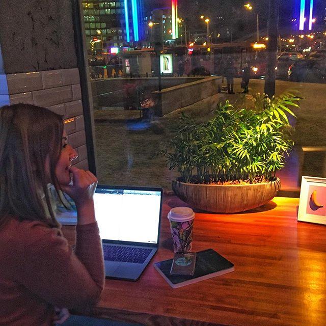 Studentin Saskia sitzt in einem Café in Kasan zum Lernen. Vor ihr ist ihr Laptop aufgeklappt, außerdem liegt ein Handy auf dem Tisch.
