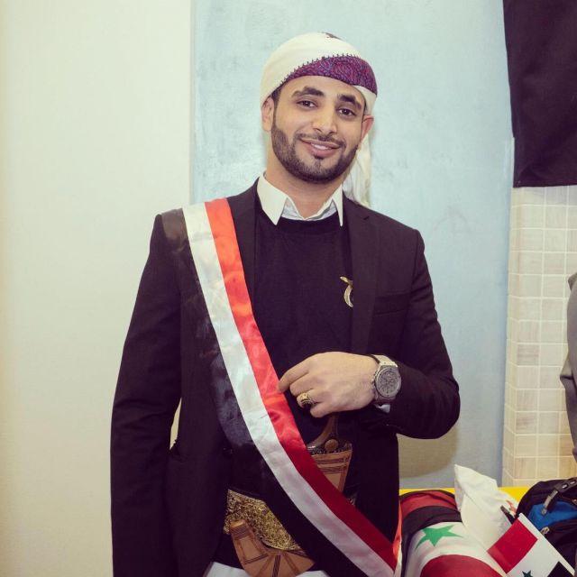 Osama in einem traditionellen Gewand mit Schere