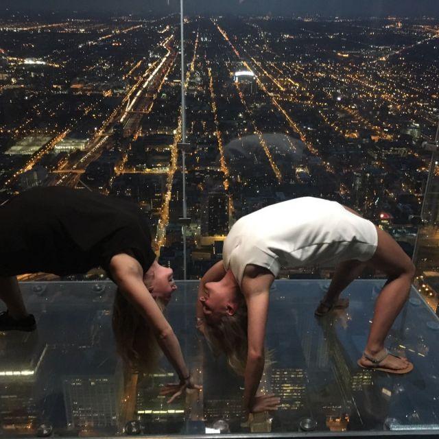 Leonie und ihre Freundin turnen auf einer Aussichtsplattform mit Blick auf eine amerikanische Großstadt bei Nacht.