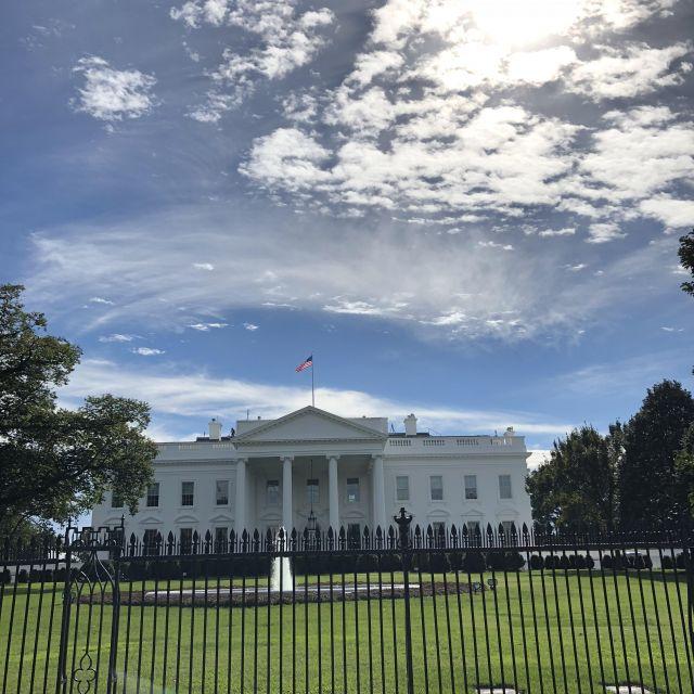Das weiße Haus von vorn. Darüber Sonnenschein und ein blauer Himmel mit ein paar Wolken.