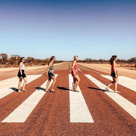 """Vier Studentinnen ahmen auf einem Zebrastreifen im sonnigen Australien das berühmte """"Abbey Road""""-Cover der Beatles nach."""