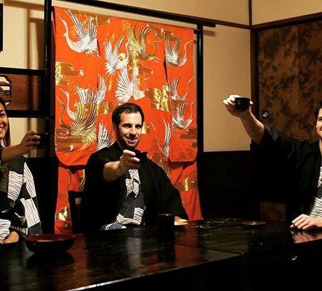 Drei junge Menschen in traditioneller japanischer Kleidung prosten sich mit Teebechern zu.