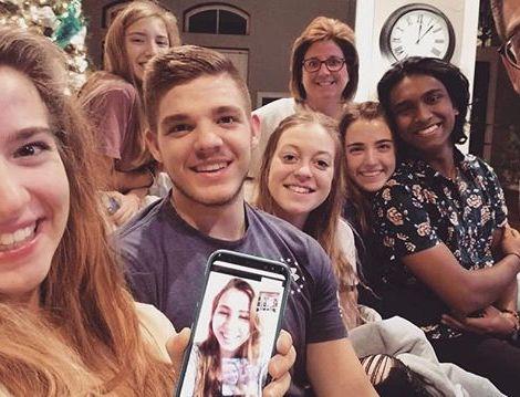 Eine Gruppe Menschen posiert für ein Familienfoto. Eine von ihnen hält ein Handy in der Hand auf dessen Bildschirm Studentin Sophie zu sehen ist.
