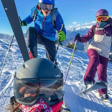 Drei junge Menschen auf Ski in Wintermontur auf einem verschneiten italienischen Berg.