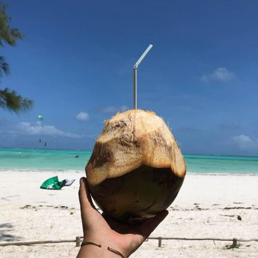 Anastasia hält eine Kokosnuss mit einem Strohhalm hoch. Im Hintergrund sieht man einen weißen Sanstrand, türkisfarbenes Wasser und einen fast wolkenlosen hellblauen Himmel.