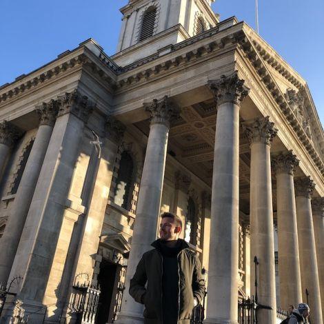 Person posiert vor einem prächtigen Gebäude