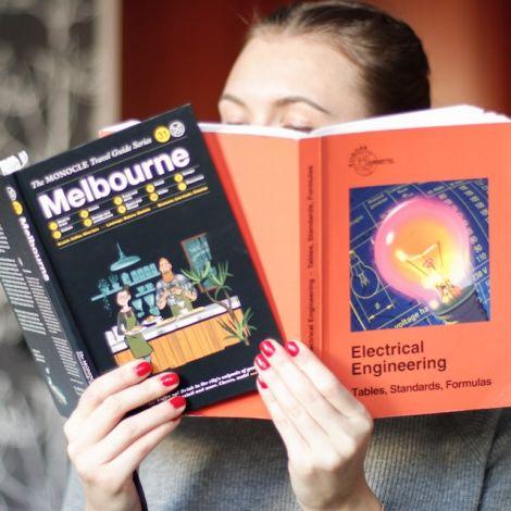 Studentin Lena liest gleichzeitig ein Buch für die Uni und einen Reiseführer für Melbourne.
