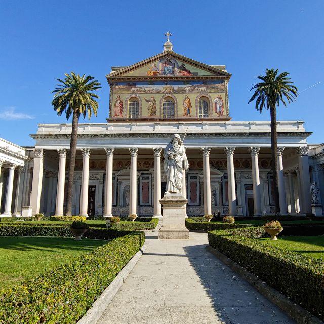 Der Vorhof der Kirche mit Statue des heiligen Paulus. Viele Säulen und Palmen sind zu sehen.