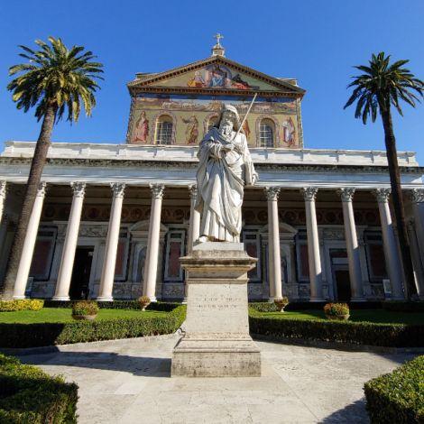 Die Paulus-Statue vor seiner Grabeskirche. Blauer Himmel, eine Wand mit Säulen und zwei Palmen sind im Hintergrund zu sehen.