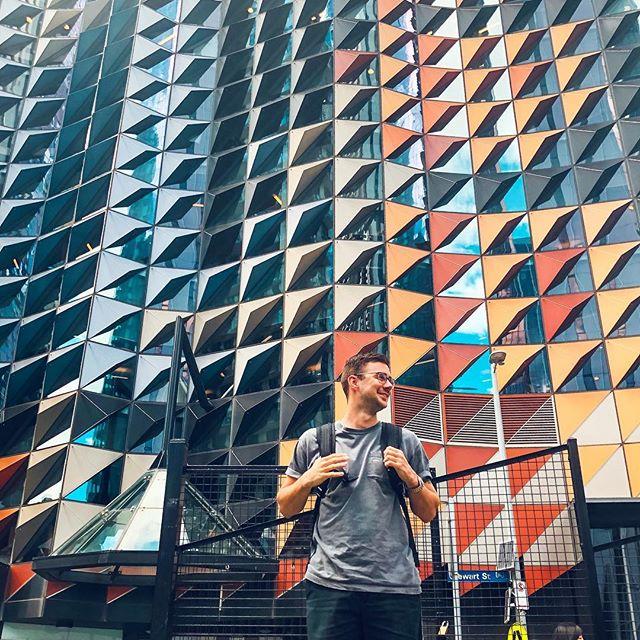 Student Philipp vor dem Gebäude der RMIT in Australien. Die Fassade besteht aus bunten und spiegelnden Dreiecken.