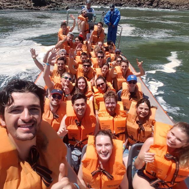 Eine Gruppe junger Menschen in dicken Schwimmwesten in einem Boot an der Wasserfällen von Iguazu.