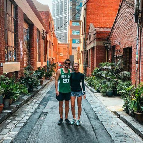 Studentin Lena und Student Philipp stehen in einer Seitenstraße in Melbourne und lächeln. Die Häuser um sie herum sind aus rotem Backstein.