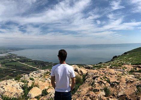 Student Benjamin steht auf einem Hügel und schaut auf den See Genezareth, der vor ihm liegt.