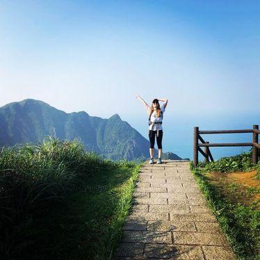 Studentin Corinna auf einem Wanderweg in Taiwan. Sie trägt Wanderkleidung und winkt fröhlich.