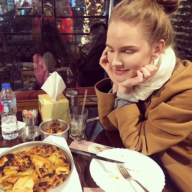 Studentin Inga schaut auf einen Teller mit Essen.