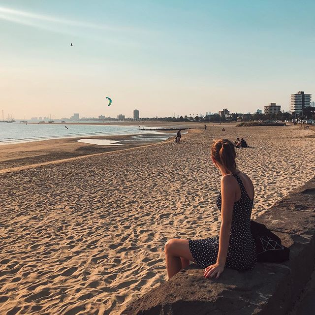 Studentin Lena sitzt am Strand in Melbourne.