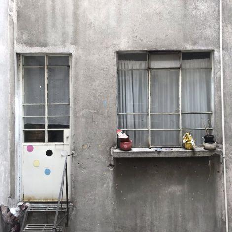 Aussicht in den Hinterhof, graue Wand, weiße Tür, Fenster mit Vorhängen