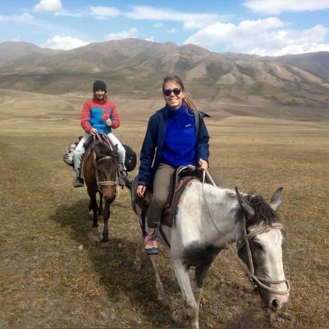 Studentin Linda reitet auf einem Pferd durch die Landschaft von Kirgistan. Sie trägt Outdoor-Kleidung und lächelt. Hinter ihr ist eine weitere junge Frau auf einem Pferd.