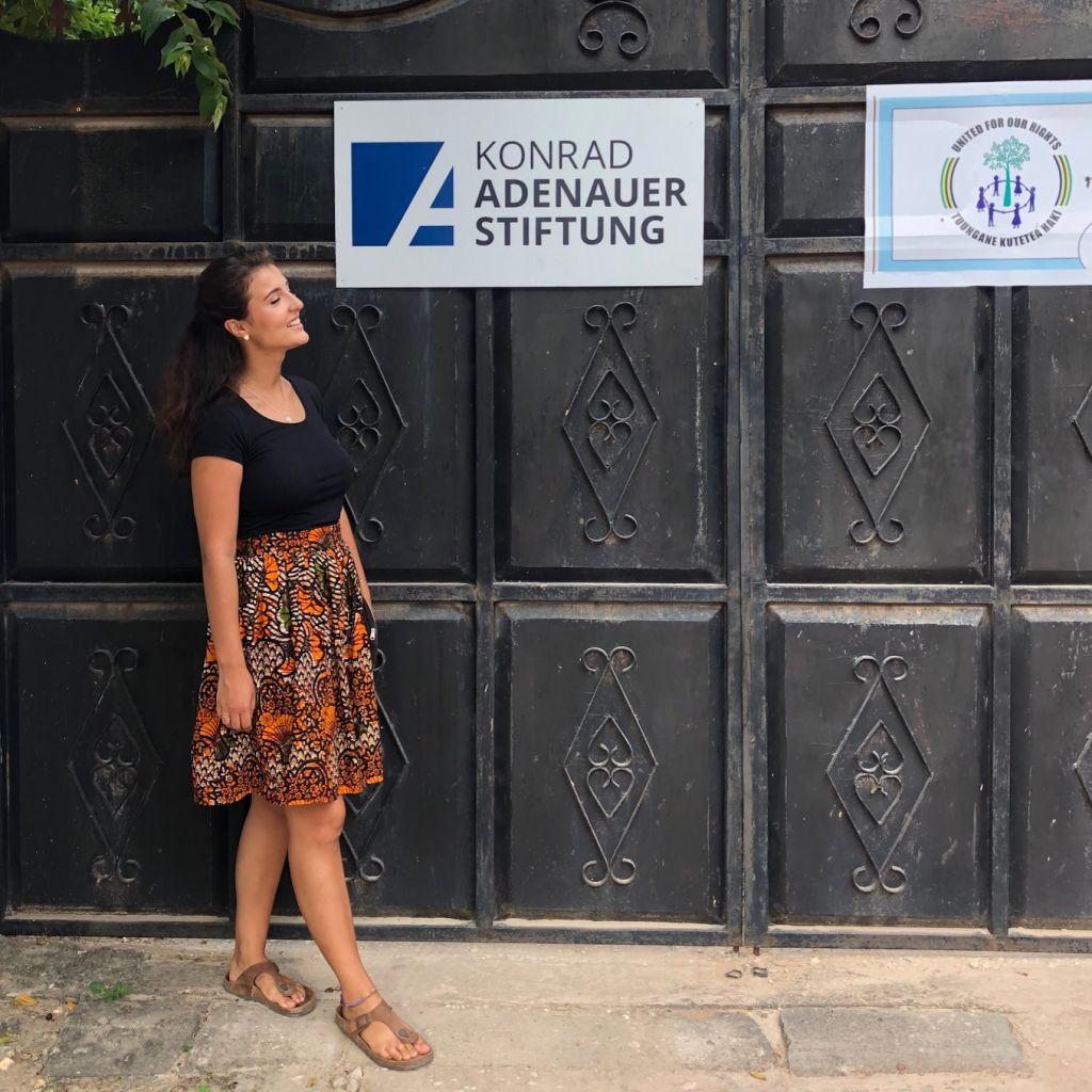 Anastasia steht vor dem Eingang der Konrad-Adenauer-Stiftung Tansania, hinter ihr das Banner