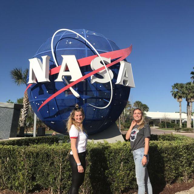 Zwei Studentinnen vor dem NASA-Logo im Kennedy Space Center.