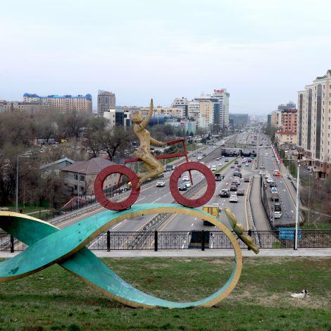 Figur eines Fahrradfahrers auf einer Brücke – unter dieser ist eine große Straße mit viel Verkehr