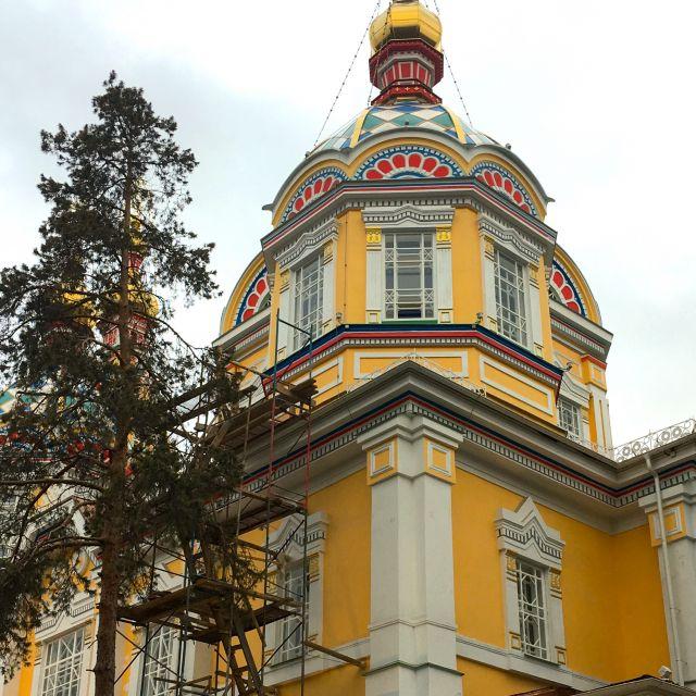 Die gelbe russisch-orthodoxe Kirche in Almaty umgeben von einem Bauzaun