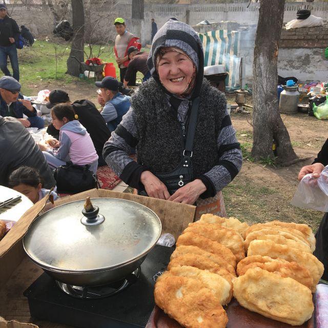 Frau verkauft Teigtaschen, die mit Kartoffeln gefüllt sind