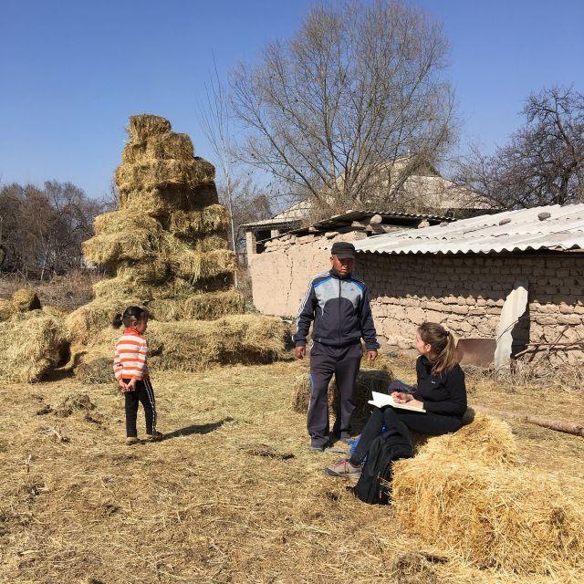 Sitze bei der Datenerhebung, vor mir ein Farmer mit seinem Kind