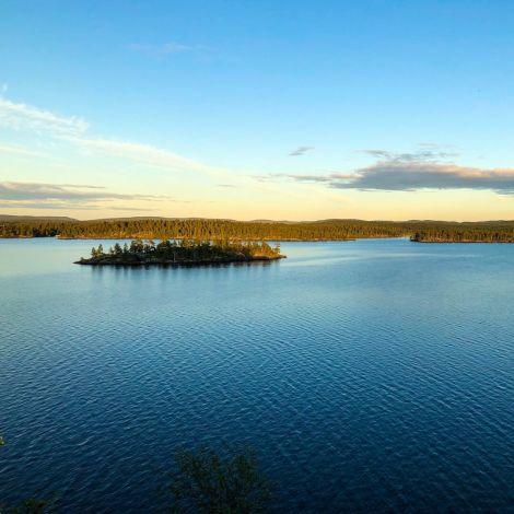 See mit ruhigem blauem Wasser, darin eine kleine Inseln mit Bäumen. Der Himmel ist klar und gold-blau.