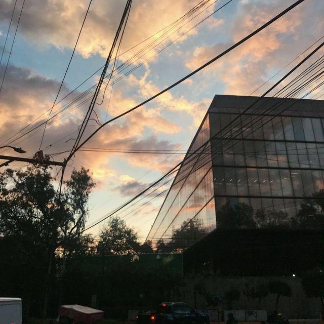 Sonnenuntergang in Coyoacan, der sich in der Fassade eines Gebäudes mit Glasfenstern spiegelt