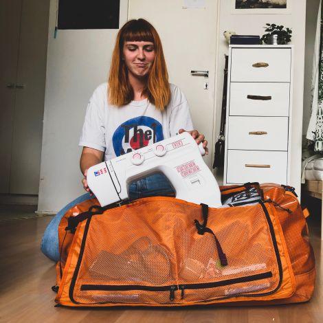 Junge Frau versucht eine Nähmaschine in eine volle Reisetasche zu packen