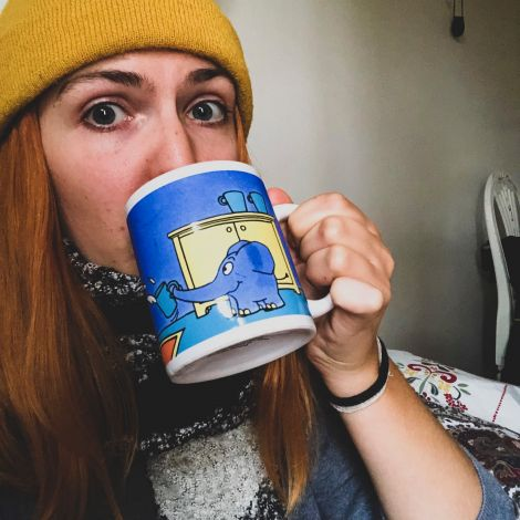 Frau bekleidet mit Mütze und Schal trinkt aus einer Tasse
