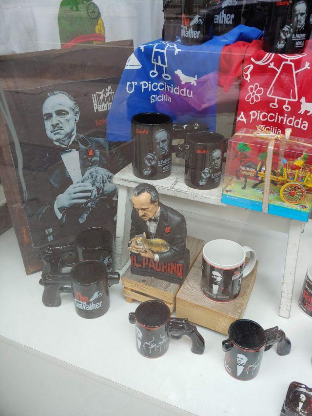 """Blick in ein typisches Schaufenster eines Souvenirladens. Hier wird mit der Filmreihe """"Der Pate"""" Geld verdient, welche die Mafia glorifiziert. Zu sehen sind T-Shirts und Tassen, die mit dem Konterfei des Paten verziert sind."""