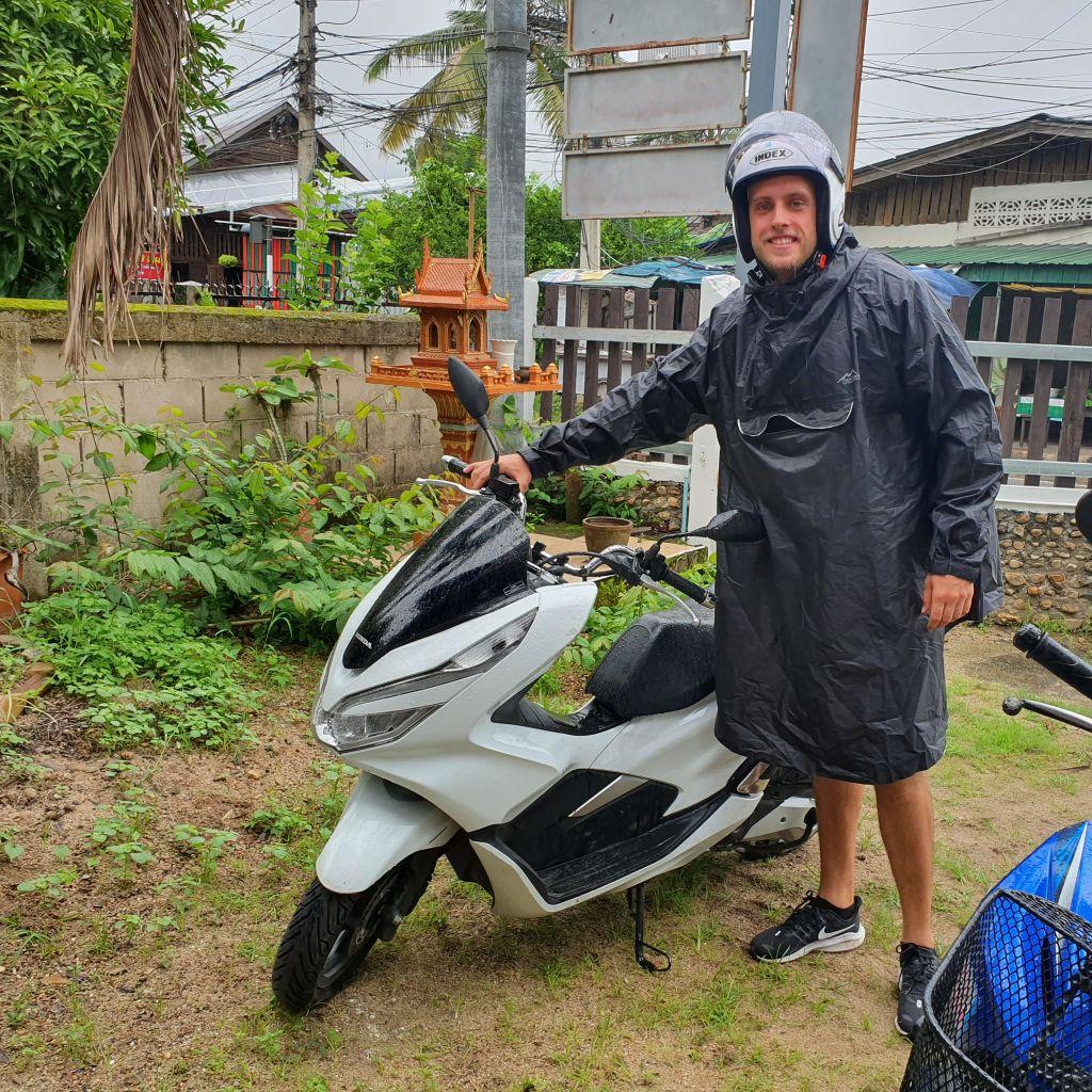 Ich im Regenponcho vor dem Roller