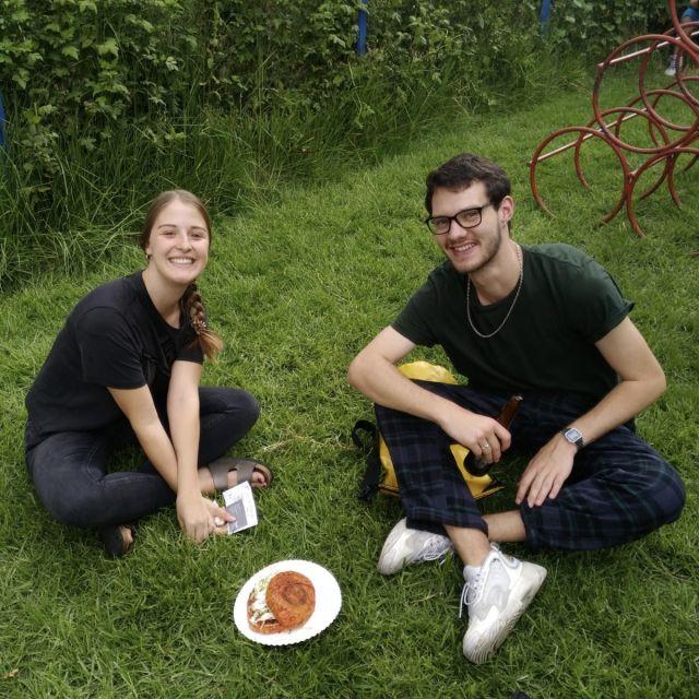 Studentin und Student lächelnd auf Rasen