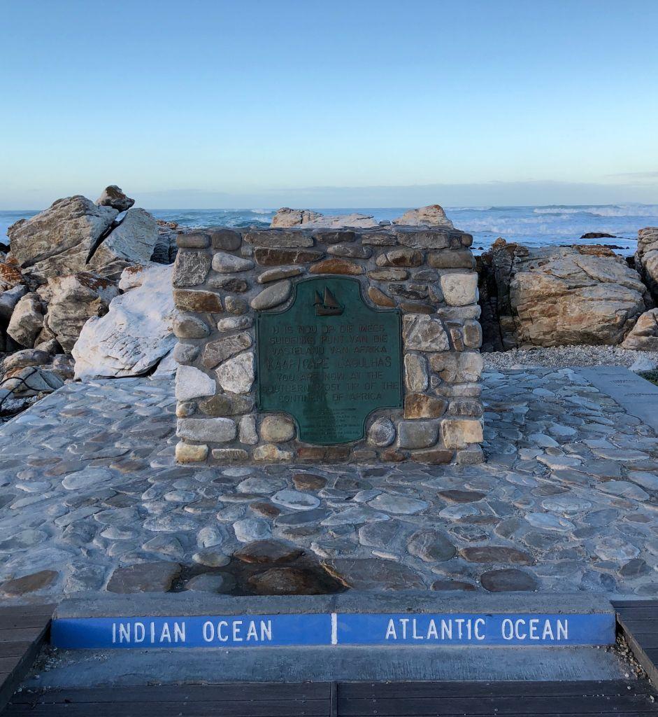 Ein Steindenkmal weist darauf hin, dass sich am südlichsten Punkt Südafrikas der Indische und der Atlantische Ozean treffen..