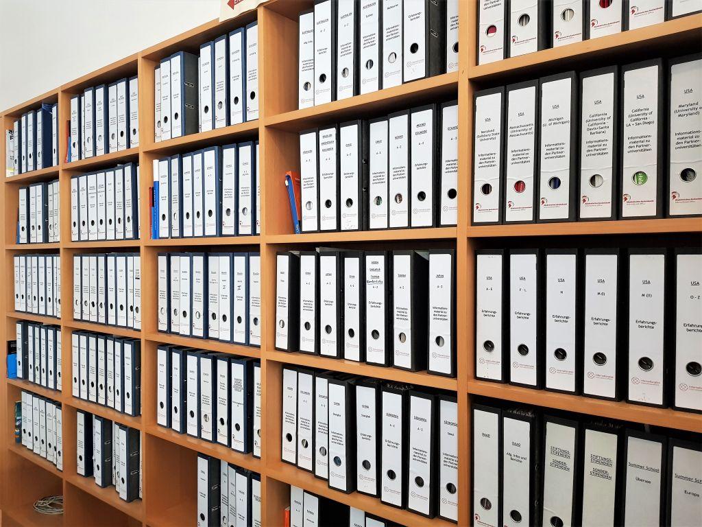 Eine Wand voller Aktenordner mit Erfahrungsberichten von anderen Studieren, die im Ausland waren.