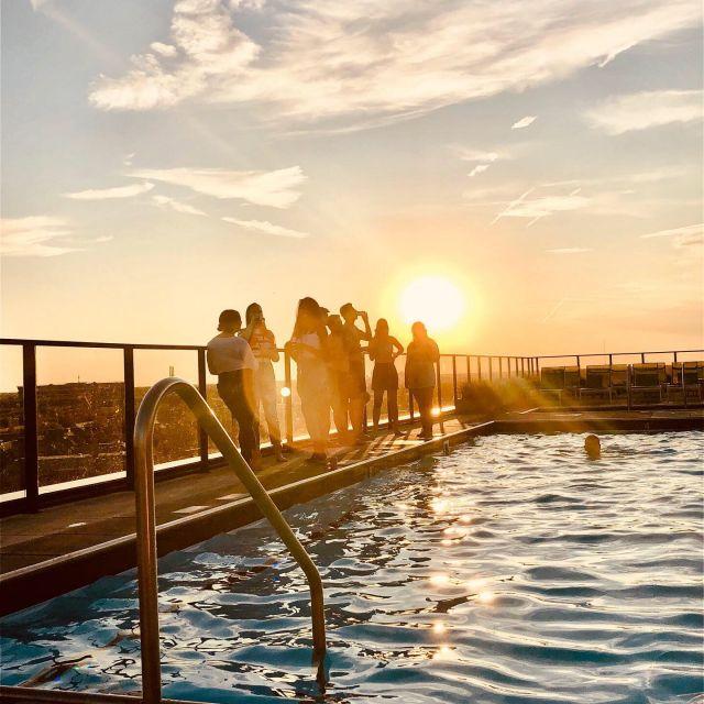 Ein Pool mit Menschen im Sonnenuntergang