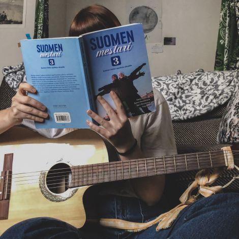 Frau mit Gitarre und Finnischbuch
