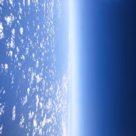Fensterausblick aus dem Flugzeug. Links befinden sich vereinzelt Wolkenspuren, rechts zeigt sich der dunkel blaue Himmel.
