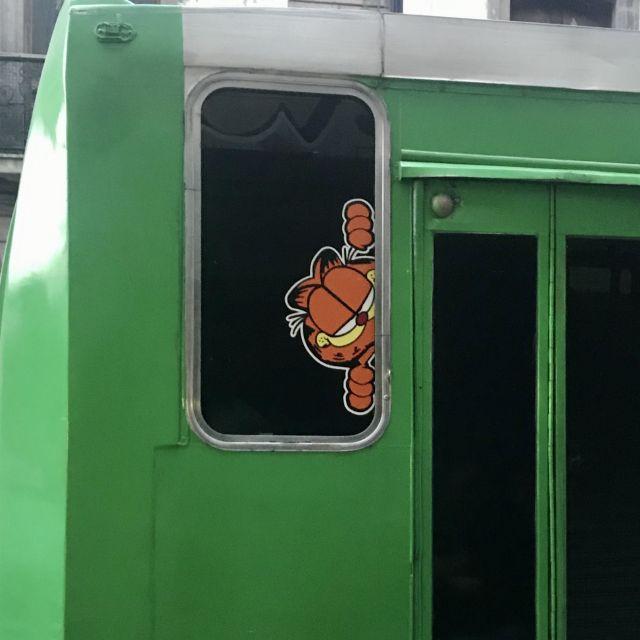 Garfield-Sticker im Fenster eines grünen Busses.