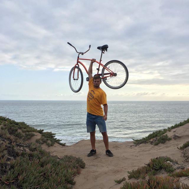 Yannic hält sein Fahrrad am Strand hoch.