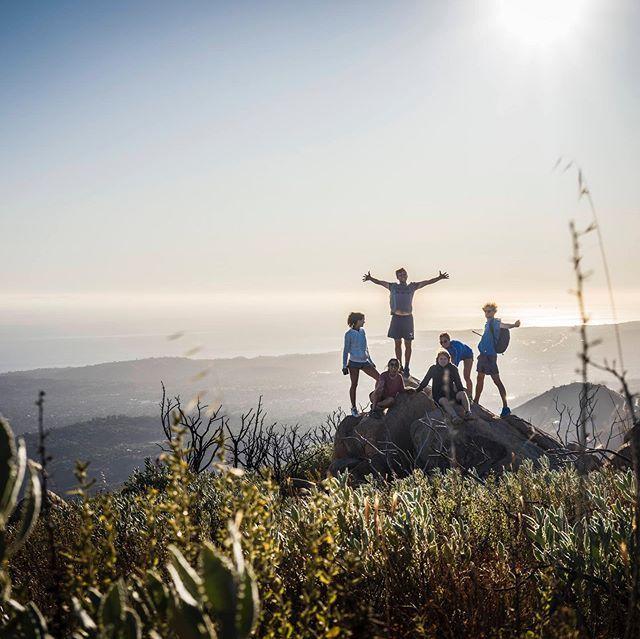 Yannic steht mit Freunden auf einem Felsbrocken auf einem Berg.