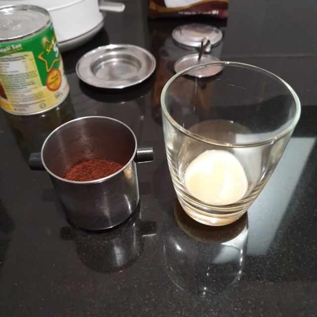 Die gesüßte Kondensmilch im Glas und daneben der Filter mit dem Kaffeepulver drin.