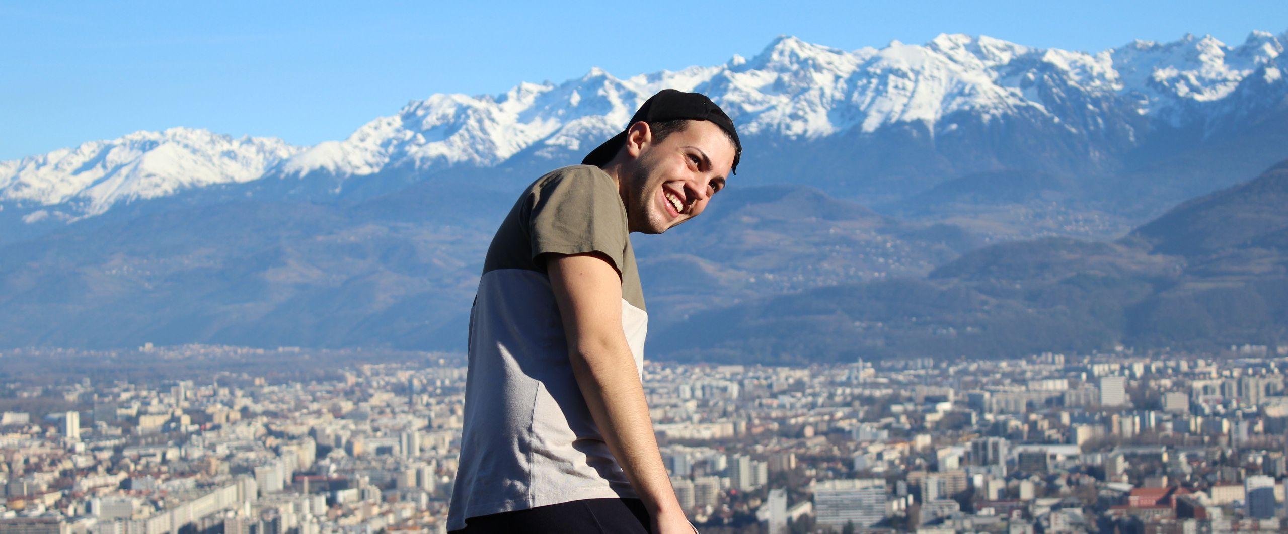 Tobi vor einer Landschaft. Ebene 1 Tobi. Ebene 2 Überblick der Stadt unten. Ebene 3 Alpenlandschaft.