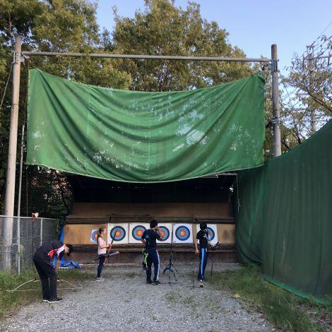 Vier Personen vom Bogenschießen-Club schießen Pfeile auf Zielscheiben.